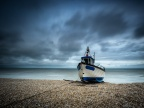 Working fishing boat on shingle beach